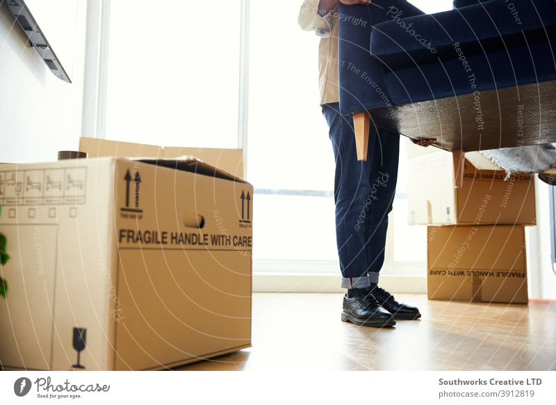 Close Up Of Man In New Home Carrying Sofa In Lounge On Moving Day Surrounded by Removal Boxes man young men house buying carrying lifting furniture sofa