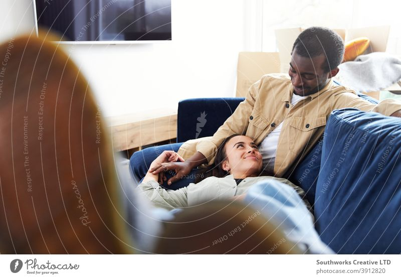 Young Couple In New Home Lying On Sofa In Lounge On Moving Day Surrounded by Removal Boxes couple young couple house buying sitting lying sofa living room