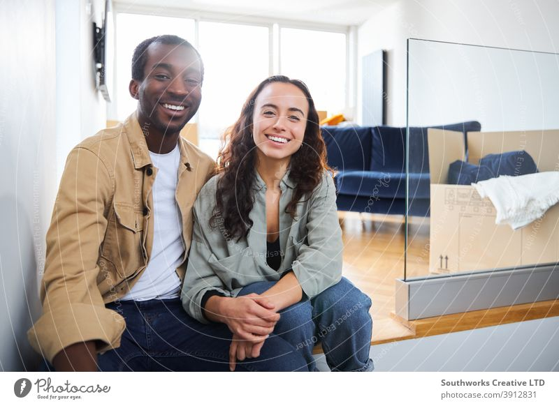 Portrait Of Young Couple Moving Into New Home Sitting On Floor In Lounge With Removal Boxes couple young couple house buying portrait looking at camera lounge