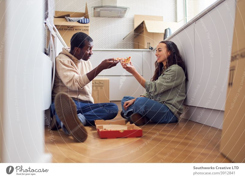 Young Couple Celebrate Moving Into New Home Sitting On Floor Eating Pizza In Kitchen With Removal Boxes couple young couple house buying pizza takeaway