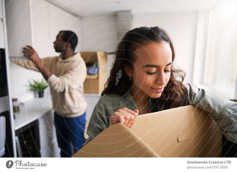 Excited Young Couple In New Home Unpacking Removal Boxes In Kitchen Together couple young couple house buying unpacking boxes home new home first home moving in