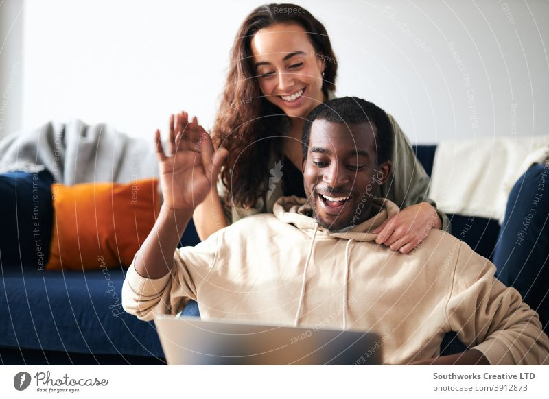 Relaxed Young Couple At Home Sitting On Sofa Making Video Call On Laptop Computer couple young couple at home laptop computer video call video chat