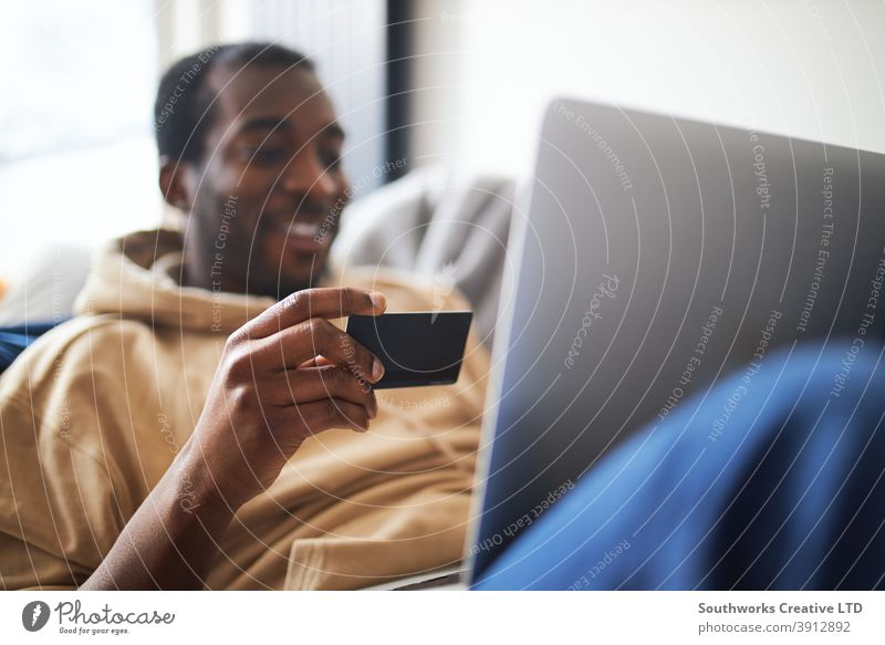 Young Man At Home Lying On Sofa With Laptop Using Credit Card To Shop Online man at home lying sofa lounge laptop computer credit card debit card pay day tech