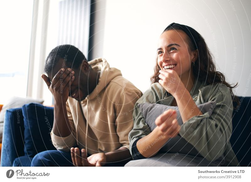 Smiling Young Couple Relaxing At Home Sitting On Sofa Cringing Whilst Watching Film On TV Together couple young couple at home sitting sofa lounge watching tv