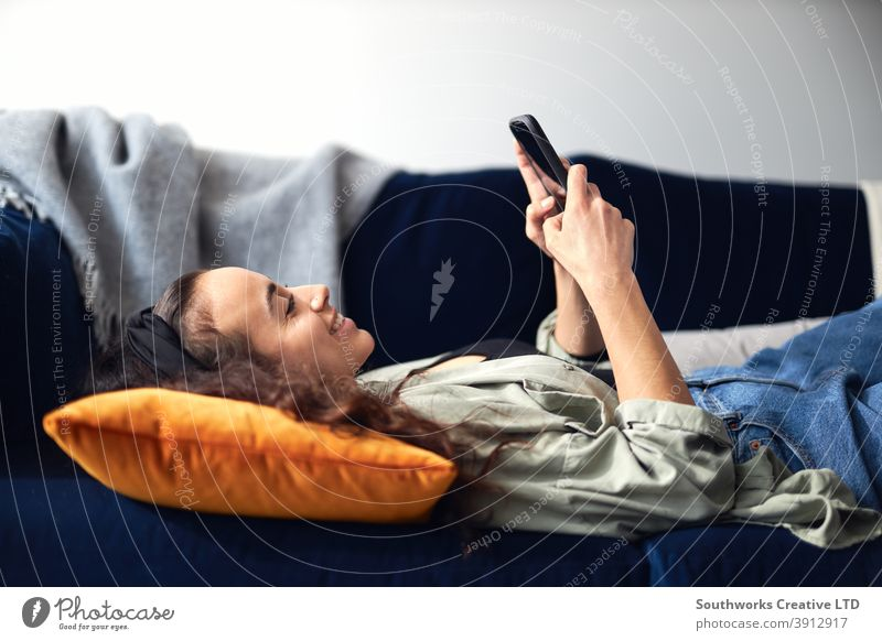 Young Smiling Woman Relaxing At Home Lying On Sofa Checking Social Media On Mobile Phone woman at home lying sofa lounge mobile mobile phone cell cell phone