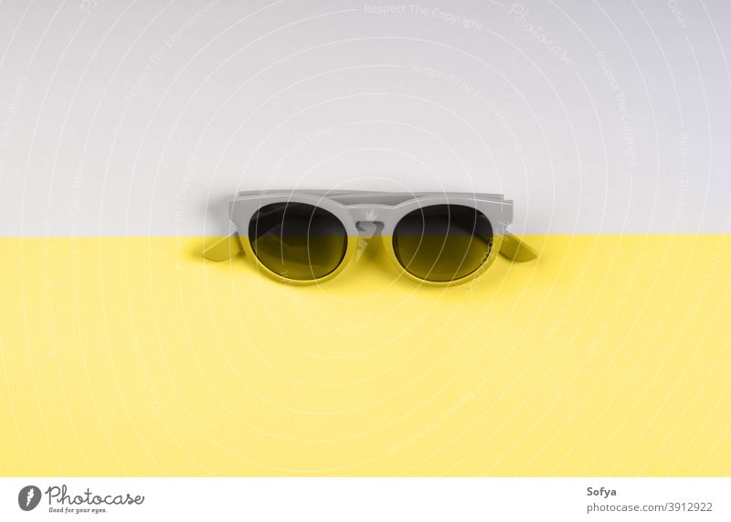 Illuminating yellow and gray sunglasses backdrop duotone illuminating color grey fashion split year ultimate background modern summer trendy object minimal