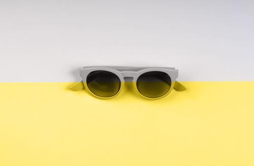 Illuminating yellow and gray sunglasses backdrop duotone illuminating color grey fashion split year ultimate background modern summer trendy object minimal
