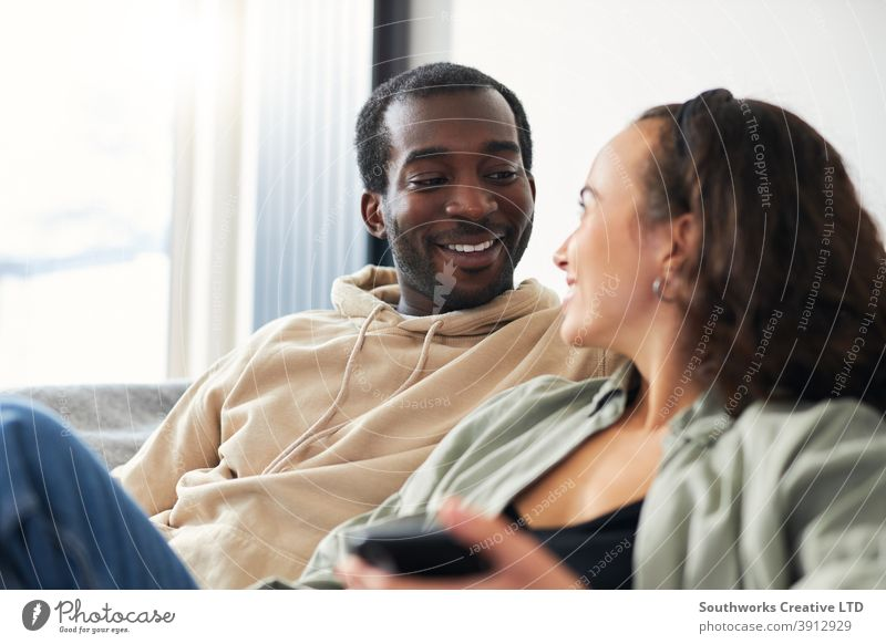 Young Smiling Couple Relaxing At Home Sitting On Sofa Checking Social Media On Mobile Phones Together couple young couple at home sitting sofa lounge mobile