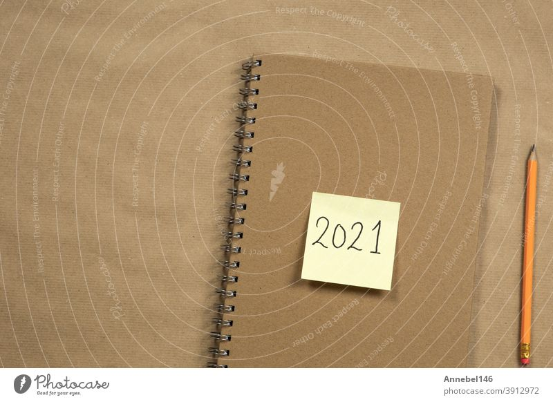 Top view of Brown notepad and yellow sticky note with 2021 new year message, pencil on brown paper background texture, education or business concept Clue Paper