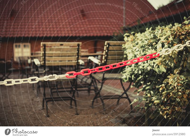 With a red and white chain cordoned off and closed outdoor area of a restaurant in the Corona pandemic in the lockdown | corona thoughts Closed Restaurant Café