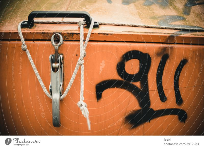 Orange garbage container tied with a rope | smeared with black paint | graffiti dustbin Trash container Recycling Waste management Waste utilization