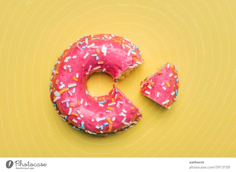 pink donut with icing on yellow background nutrition fast baked pastry item glazed donuts cookie flavor temptation candy sweet food multi colored closeup
