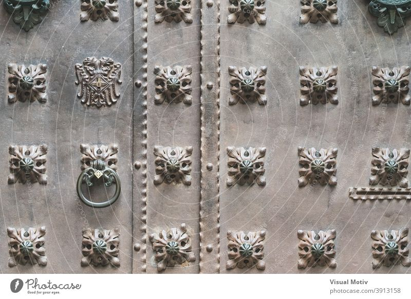 Close-up of an old iron door with decorative studs front architecture detail abstract close-up aged urban ornamental background knocker metallic