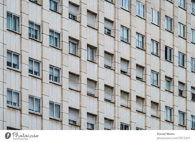 Rows of windows with roller shutters on the facade of an urban building architecture exterior structure construction metropolitan edifice abstract modern rows