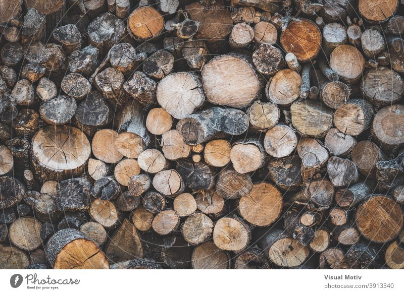 Detail of stacked wooden logs prepared to be used as firewood countryside rustic woodpile resource texture background natural various timber rural structure