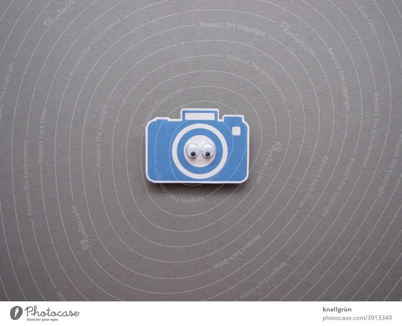 Small blue paper camera with two wiggle eyes wobbly eyes Looking Eyes Looking into the camera Paper Low-cut Colour photo Blue White Gray Black