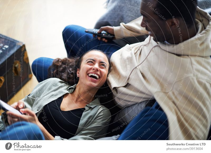 Overhead shot of relaxed young couple at home on sofa watching TV and checking cell phone Couple Sit Sofa Lounge TV set Television Mobile Cellphone technology