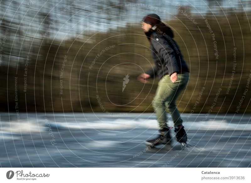 Young man skating on the frozen pond Athletic Lake trees Joy swift Cold and frost Ice Winter fun skates ice skating Landscape Tree Green Gray winter jacket Cap