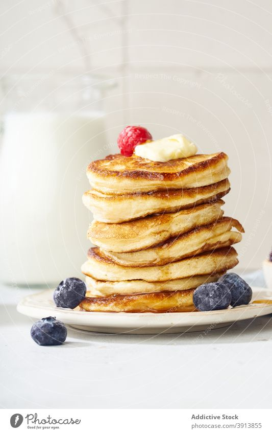 A stack of buttermilk pancakes breakfast food fluffy dessert delicious sirup meal sweet homemade white maple gold plate honey pile fresh morning baked snack
