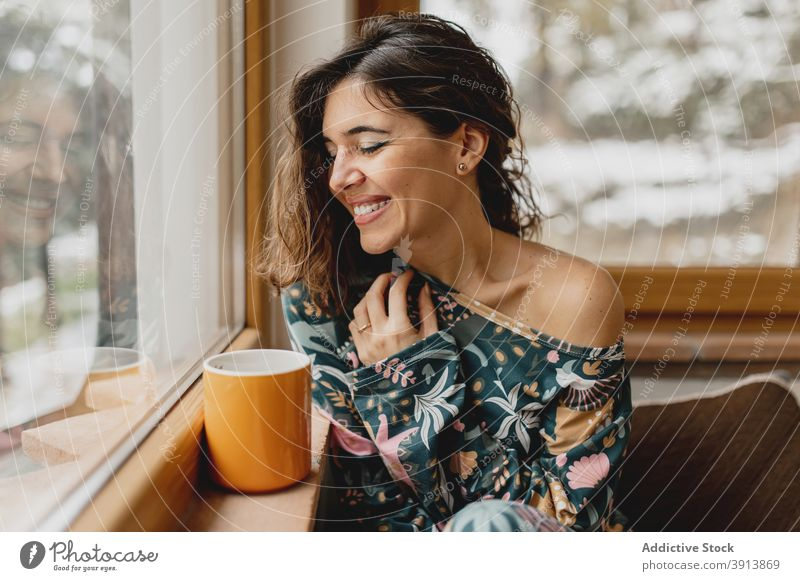 Close up vertical caucasian attractive woman portrait smiling with a cup of hot beverage. sleepwear vacancy cozy rural girl coffee tea person snow closeup