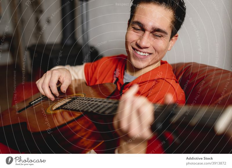 Close up young man portrait holding and playing the guitar cozy music stay at home guitarist fireplace person acoustic player handsome winter holiday student