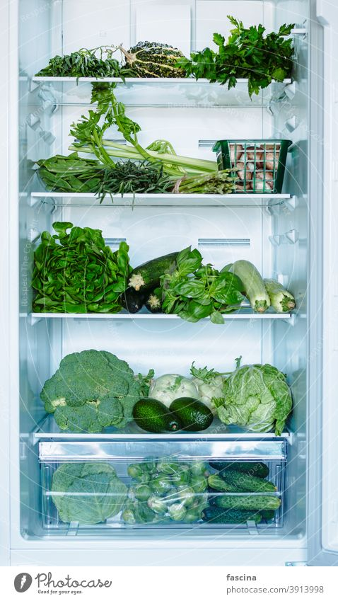 Green vegetables and greens in open refrigerator full fridge food fresh diet freezer kitchen cold domestic freshness home healthy lifestyle natural nutrition