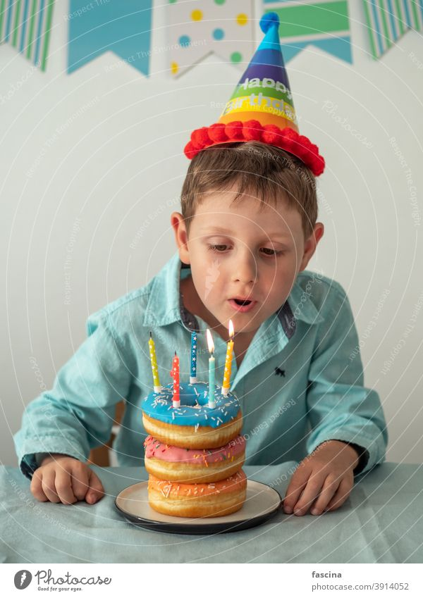 Child blows out the candle on birthday donuts cake boy hands five year his little child hold plate doughnut fun five-year-old happy sprinkles food sweet dessert