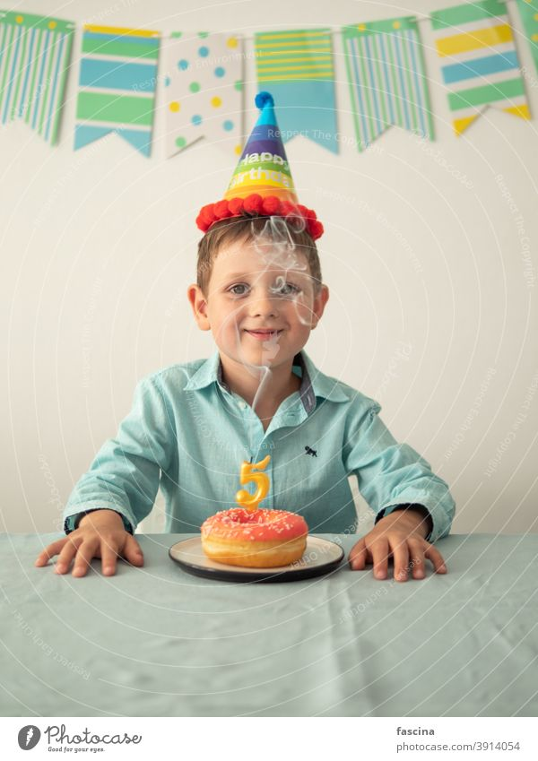 Child through smoke from candle on festive donut birthday boy hands five year his little smiling child hold plate doughnut looking at camera smile fun