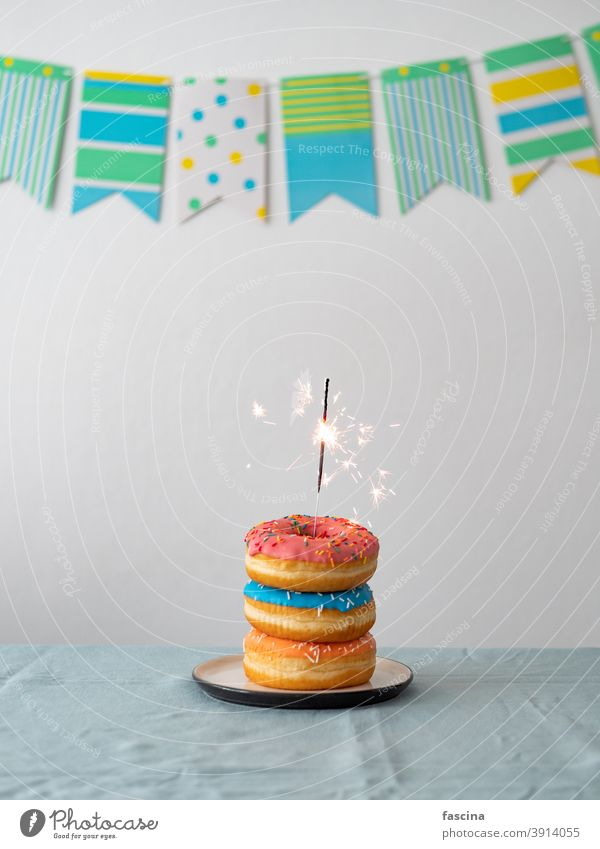 Birthday donuts cake with sparkler on table bengal light birthday garland birthday donuts stack sweet delicious doughnuts party flag background vertical copy
