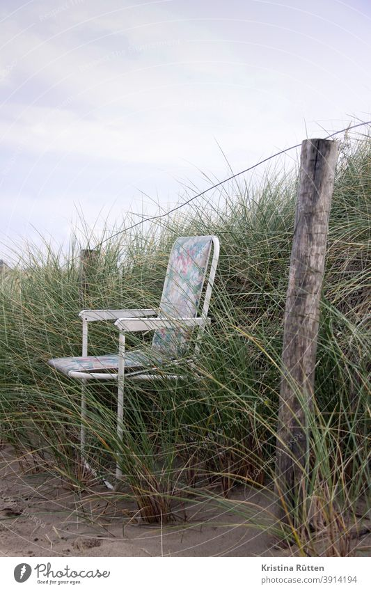 folding chair in dune grass Camping chair Folding chair Garden chair Chair Fence turned off Forget forsake sb./sth. out dunes Marram grass Grass Sand Nature