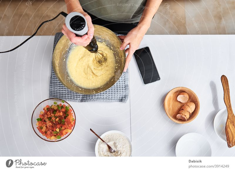 Woman in kitchen cooking a cake. Hands beat the dough with an electric mixer, top view woman recipe ingredients food person home female caucasian diet meal