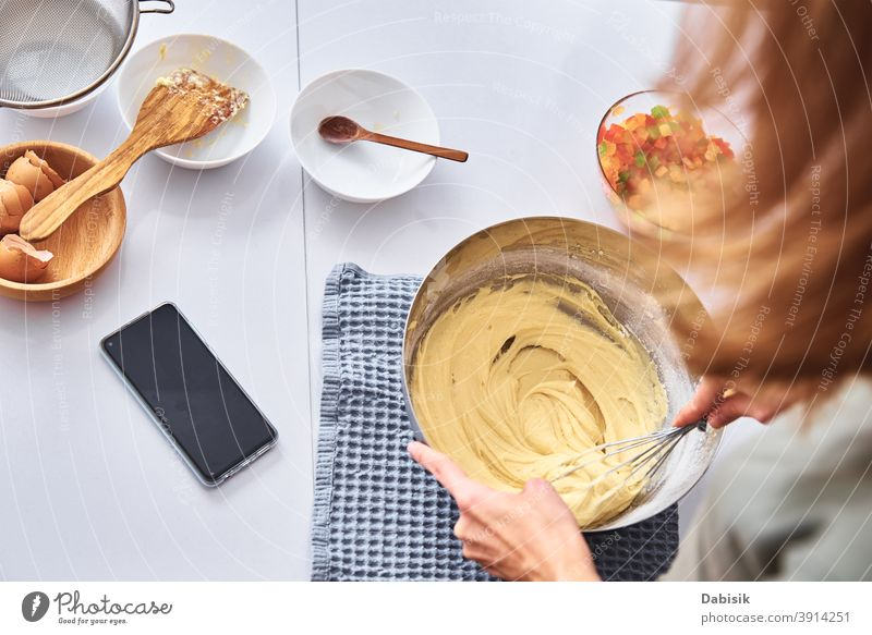 Woman in kitchen cooking a cake. Hands beat the dough with mixer woman recipe ingredients food person home female caucasian diet meal lifestyle prepare people