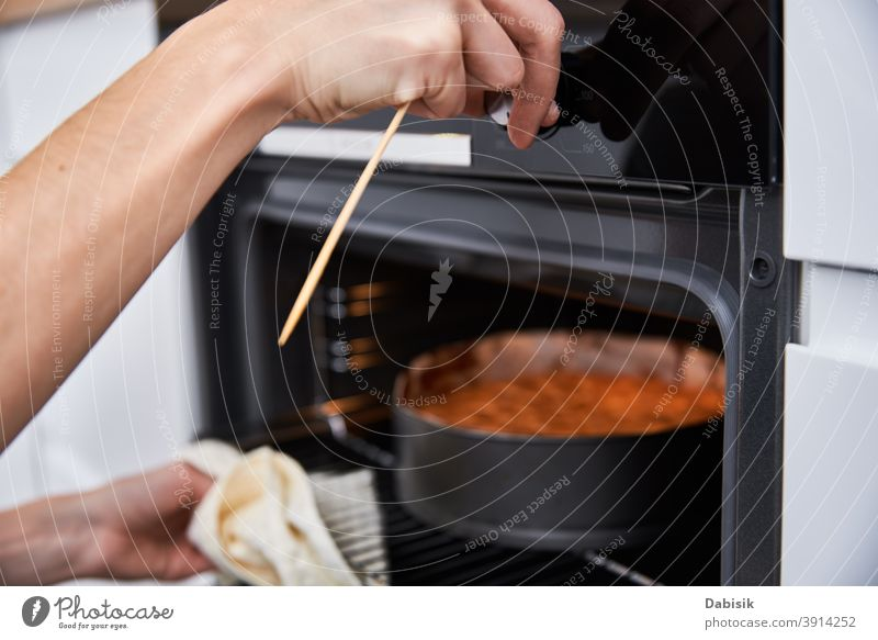 Housewife prepare cake in kitchen. Homemade cake baking in oven bake making housewife woman dish fresh hand home pie plate bakery cook cooking cuisine delicious