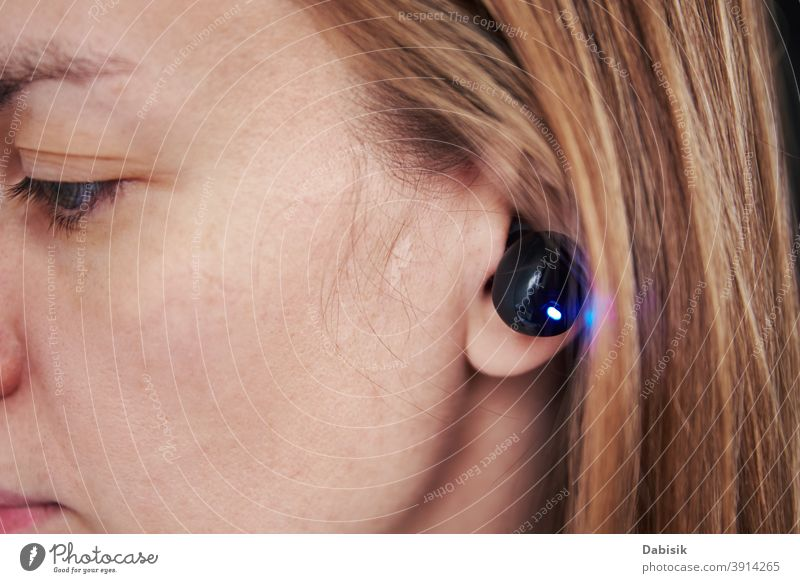 Woman listening music through wireless earphones. Caucasian woman using bluetooth headhones in the ear, close up audio black headphone equipment digital