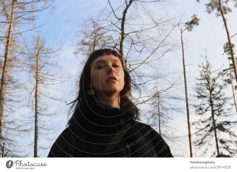Portrait of a young woman looking down under bare treetops Face of a woman portrait Woman Identity Long-haired feminine Self-confidence Self-confident