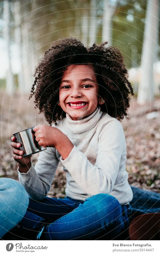 portrait of cute afro kid girl outdoors doing picnic, holding mug of water, autumn season, beautiful trees background nature golden hour hat brown leaves