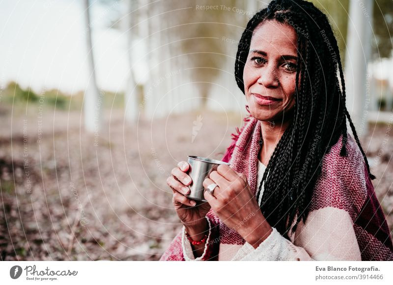 portrait of hispanic mid adult woman outdoors holding wrapped in blanket. Holding mug of water water during picnic.Autumn season autumn afro woman latin sunset