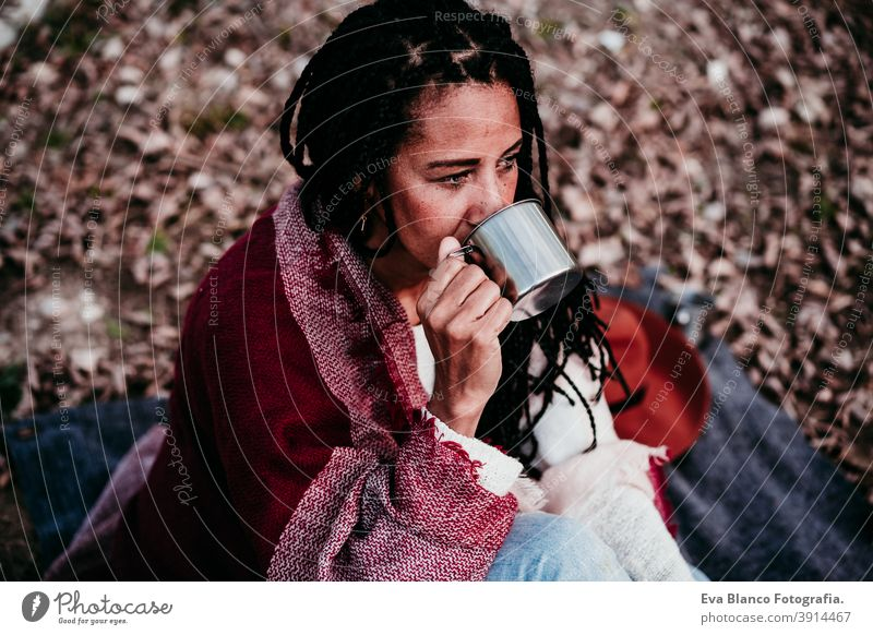portrait of hispanic mid adult woman outdoors holding wrapped in blanket. drinking water during picnic.Autumn season autumn afro woman latin sunset nature hat