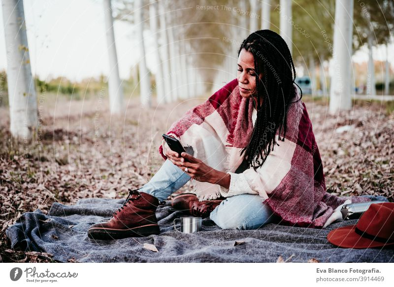 portrait of hispanic mid adult woman outdoors holding wrapped in blanket. Using mobile phone during picnic.Autumn season autumn afro woman latin sunset nature