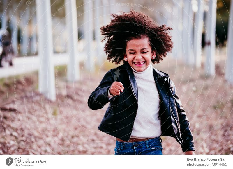 portrait of cute afro kid girl running at sunset during golden hour, autumn season, beautiful trees background fun nature outdoors hat brown leaves