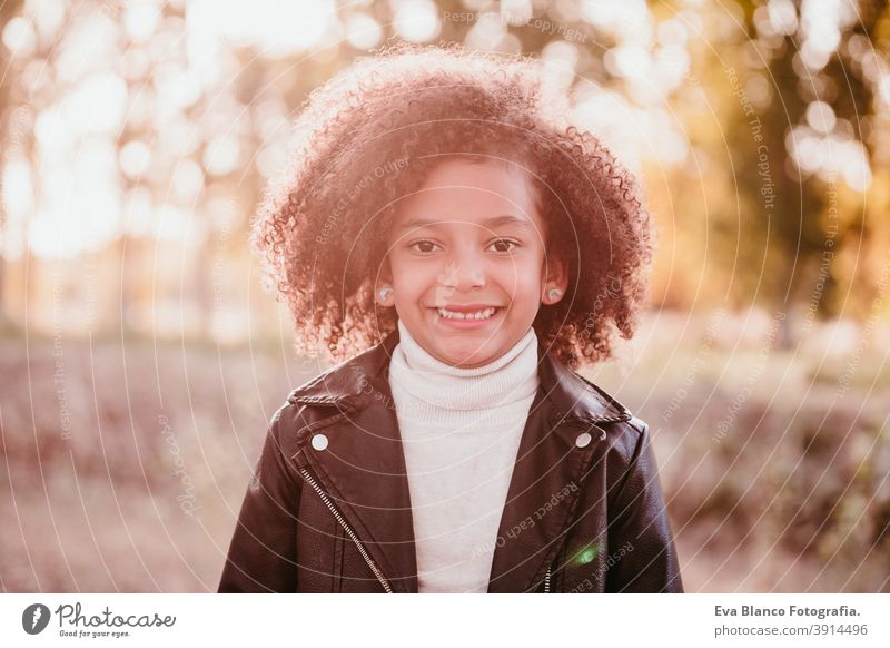 portrait of cute afro kid girl smiling at sunset during golden hour, autumn season, beautiful trees background nature outdoors hat brown leaves casual clothing
