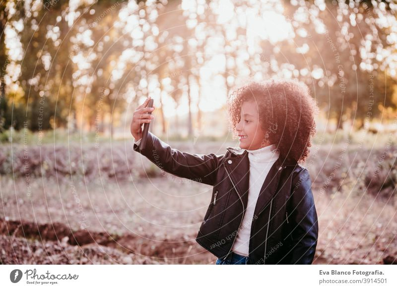 portrait of cute afro kid girl using mobile phone at sunset during golden hour, autumn season, beautiful trees background technology nature outdoors hat brown