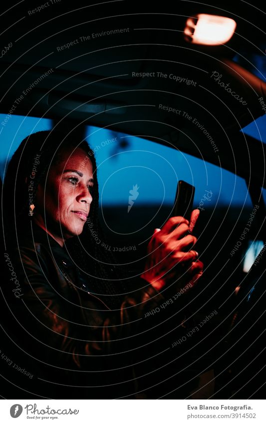hispanic woman using mobile phone in car at night. Travel and technology concept screen travel beautiful mid adult lifestyles smart fun vehicle inside young