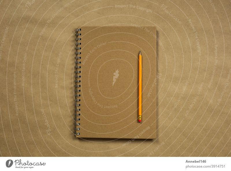 Brown notebook and classic pencil on brown plain paper background texture, copy space or space for text, business or education concept top view modern retro design