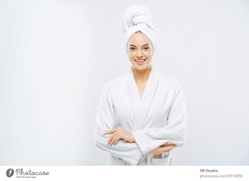 Beautiful smiling young woman has soft healthy skin after taking shower, wears bath robe and towel wrapped on head, enjoys spare time at home, isolated over white background. Wellness concept.