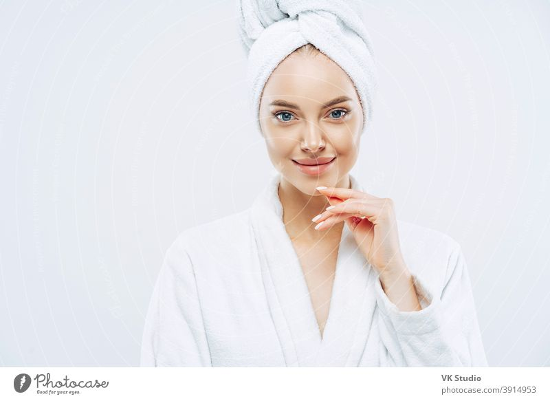 Studio shot of pretty beauty woman has washed hair, wears wrapped towel on head, has manicure, cute natural face, touches chin gently, looks with tender smile, dressed in bath robe, poses indoor