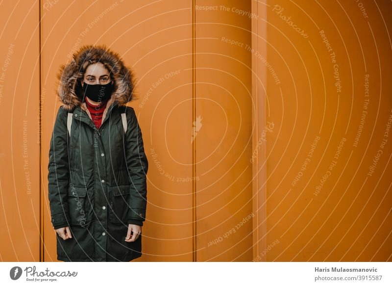 woman with face mask standing against orange city wall adult attractive beautiful beauty blonde bus station caucasian confident coronavirus covid-19 croatia
