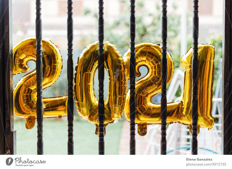 Gold foil balloons numeral 2021 behind bars confined starting the year. coronavirus crisis concept. Balloons jail confines confinement gold new year beginning