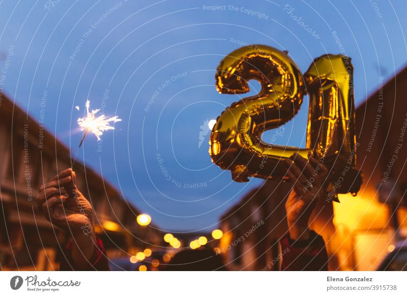 Celebrating with Gold foil balloons numeral 21 and sparkler at night. Happy New year 2021 celebration. numbers years sparkles congratulations glossy concepts