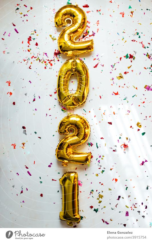 Gold foil balloons numeral 2021 with colorful confetti on white background. Happy New year 2021 celebration. numbers years invitation congratulations glossy